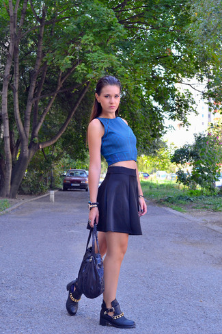 A blue t-shirt and a navy skater skirt are a great outfit formula to have in your arsenal. A cool pair of black cutout leather ankle boots is an easy way to upgrade your look.