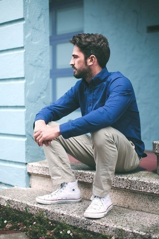 How to Wear Beige Chinos: This combination of a blue dress shirt and beige chinos is hard proof that a safe look doesn't have to be boring. If you need to immediately play down your ensemble with one piece, complement your look with white canvas high top sneakers.