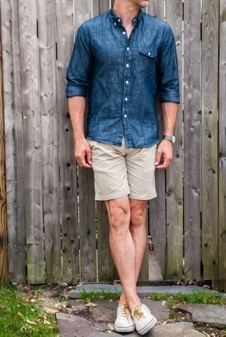 How to Wear a Blue Chambray Long Sleeve Shirt For Men: This is solid proof that a blue chambray long sleeve shirt and beige shorts are awesome when matched together in a laid-back menswear style. Complement your ensemble with white canvas low top sneakers and you're all done and looking boss.