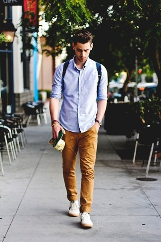 A blue long sleeve shirt and tobacco chinos is a great combination to add to your styling repertoire. A good pair of white low top sneakers are sure to leave the kind of impression you want to give.