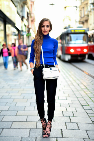 A blue turtleneck and black slim pants are a combination that every stylish girl should have in her wardrobe. Complement this look with black suede heeled sandals.