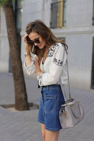 Cómo combinar: blusa campesina bordada en blanco y negro, falda con botones vaquera azul, bolso bandolera de cuero gris