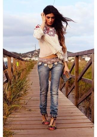 Cómo combinar: blusa campesina bordada blanca, vaqueros azules, sandalias de tacón de ante en multicolor, cartera sobre de cuero estampada negra
