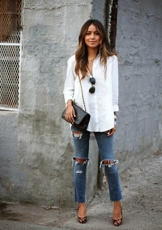 Una blusa de botones blanca y unos vaqueros pitillo desgastados azules son el combo perfecto para llamar la atención por una buena razón. Este atuendo se complementa perfectamente con zapatos de tacón de cuero de leopardo marrón claro.