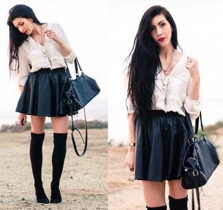 Opta por una blusa de botones blanca y una falda skater de cuero negra para crear una apariencia elegante y glamurosa. ¿Por qué no ponerse botas sobre la rodilla de ante negras a la combinación para dar una sensación más clásica?