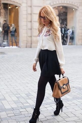 Cómo combinar: blusa de botones bordada blanca, falda skater negra, botines de ante negros, bolso de hombre de cuero marrón claro