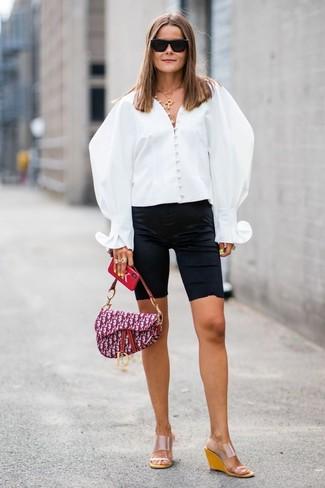 Cómo combinar: blusa de botones blanca, mallas ciclistas negras, sandalias con cuña de goma transparentes, bolso de hombre de lona estampado morado