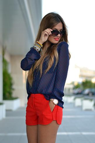 Elige una blusa de botones a lunares azul marino y unos pantalones cortos para una apariencia fácil de vestir para todos los días.