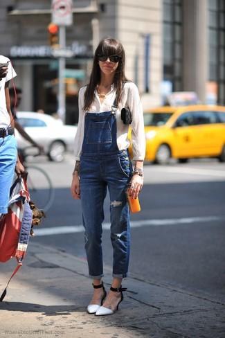 Cómo combinar: blusa de botones blanca, peto vaquero azul, zapatos de tacón de cuero en blanco y negro, cartera sobre de ante negra