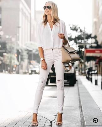 Cómo combinar: blusa de botones de seda blanca, vaqueros pitillo desgastados blancos, sandalias de tacón de cuero en beige, bolsa tote de cuero marrón claro