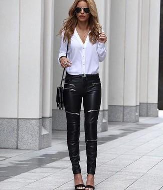 Cómo combinar: blusa de botones blanca, vaqueros pitillo de cuero negros, sandalias de tacón de cuero negras, bolso bandolera de cuero negro