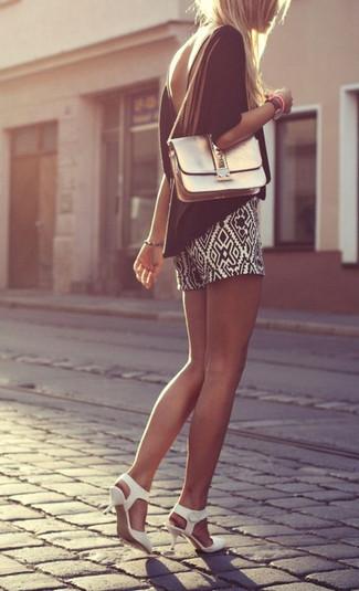 Cómo combinar: blusa de manga corta negra, pantalones cortos con estampado geométrico en negro y blanco, zapatos de tacón de cuero blancos, bolso bandolera de cuero dorado