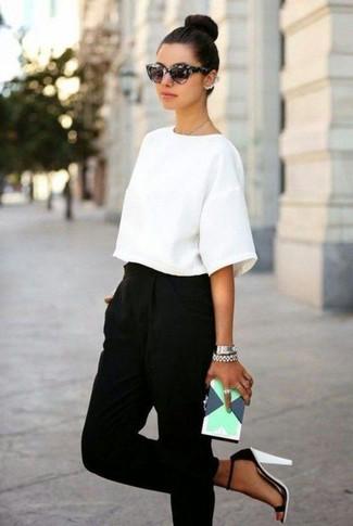 Cómo combinar: blusa de manga corta blanca, pantalón de pinzas negro, sandalias de tacón de cuero en blanco y negro, cartera sobre de cuero con estampado geométrico en verde menta