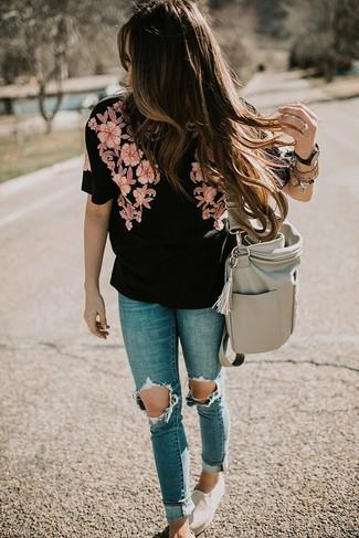 Cómo combinar: blusa de manga corta bordada negra, vaqueros pitillo desgastados azules, zapatillas slip-on de lona en beige, bolsa tote de cuero gris