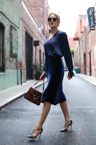 Cómo combinar: blusa de manga larga de satén azul marino, falda midi de terciopelo azul marino, zapatos de tacón de cuero negros, bolso de hombre de cuero burdeos
