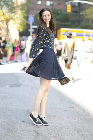 Cómo combinar: blusa de manga larga de estrellas azul marino, minifalda de gasa plisada azul marino, tenis de lona negros, bolso bandolera de cuero en marrón oscuro