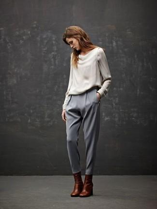 Cómo combinar: blusa de manga larga de seda blanca, pantalón de pinzas gris, botines de cuero marrónes