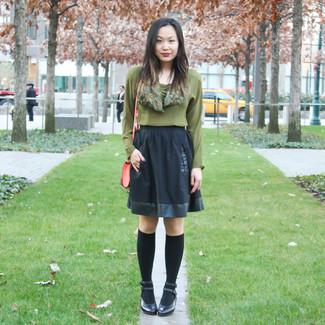 Cómo combinar: blusa de manga larga verde oliva, falda skater negra, zapatos de tacón de cuero negros, calcetines hasta la rodilla negros