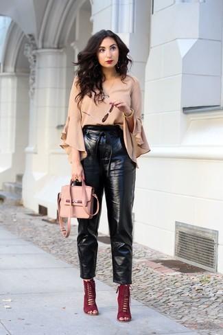 Cómo combinar: blusa de manga larga con volante en beige, pantalón de pinzas de cuero negro, sandalias de tacón de ante burdeos, bolso bandolera de cuero rosado