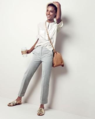 Cómo combinar: blusa de manga larga blanca, pantalón de vestir gris, sandalias planas de cuero сon flecos doradas, bolso bandolera de cuero marrón claro