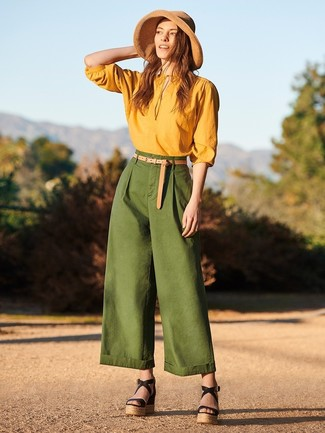 Cómo combinar: blusa de manga larga mostaza, pantalones anchos verde oscuro, sandalias con cuña de cuero negras, sombrero de paja marrón claro