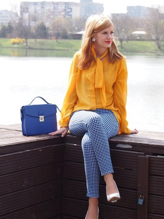 Para seguir las tendencias usa una blusa de manga larga amarilla y unos pantalones pitillo a cuadros en blanco y azul. Este atuendo se complementa perfectamente con zapatos de tacón de cuero blancos.