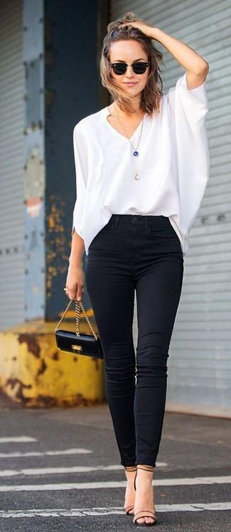 Una blusa de manga larga blanca y unos vaqueros pitillo negros son el combo perfecto para llamar la atención por una buena razón. Completa el look con sandalias de tacón de cuero marrón claro.
