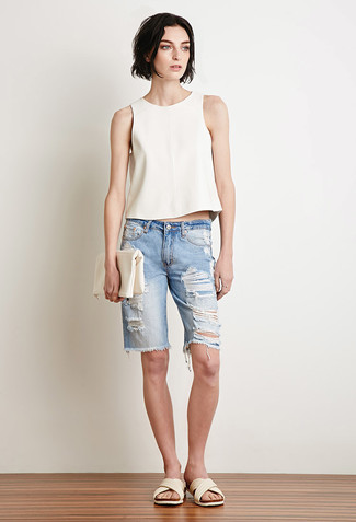 Cómo combinar: blusa sin mangas blanca, bermudas vaqueras desgastadas celestes, sandalias planas de cuero blancas, cartera sobre de cuero blanca