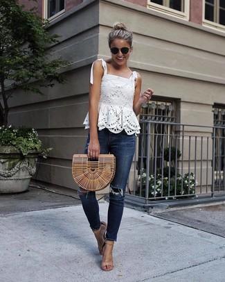 Cómo combinar: blusa sin mangas de encaje blanca, vaqueros pitillo desgastados azul marino, sandalias de tacón de cuero marrón claro, cartera sobre de paja marrón claro