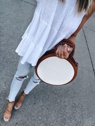 Cómo combinar: blusa sin mangas blanca, vaqueros pitillo desgastados celestes, sandalias con cuña de cuero marrón claro, bolso bandolera de paja blanco