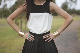 Cómo combinar: blusa sin mangas en blanco y negro, falda skater negra, pulsera dorada, anillo dorado