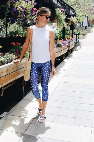 Cómo combinar: blusa sin mangas blanca, leggings estampados azules, sandalias planas de cuero blancas, bolsa tote de paja en beige