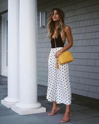 Cómo combinar: blusa sin mangas negra, falda pantalón a lunares en blanco y negro, sandalias de tacón de goma transparentes, bolso bandolera de cuero amarillo
