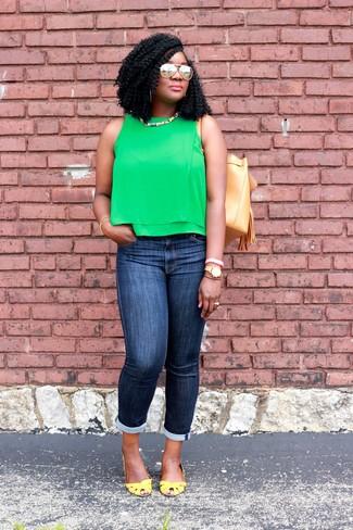 Cómo combinar: blusa sin mangas verde, vaqueros pitillo azul marino, zapatos de tacón de cuero amarillos, mochila con cordón de cuero marrón claro