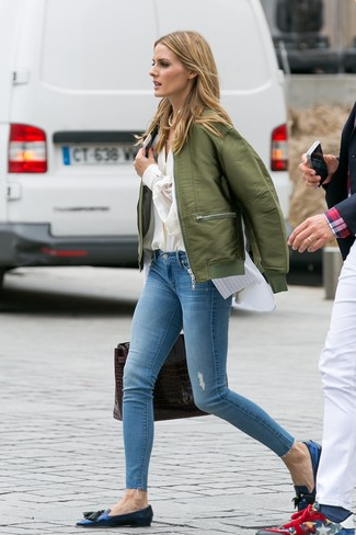 How to wear: olive bomber jacket, beige button down blouse, white vertical striped sleeveless button down shirt, light blue ripped skinny jeans