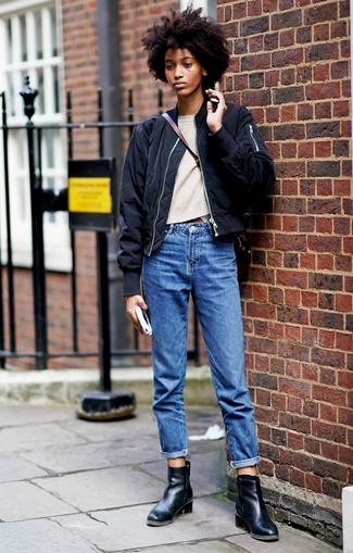 How to wear: black bomber jacket, beige crew-neck sweater, blue boyfriend jeans, black leather ankle boots