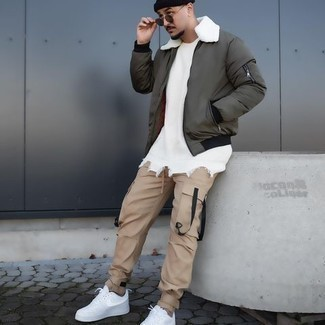 Olive Bomber Jacket Outfits For Men: If you're a fan of classic combos, then you'll appreciate this combo of an olive bomber jacket and khaki cargo pants. If you're on the fence about how to finish, a pair of white canvas low top sneakers is a fail-safe option.