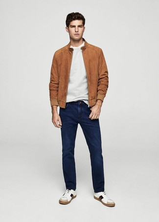 How to wear: tobacco suede bomber jacket, grey crew-neck sweater, white crew-neck t-shirt, navy jeans