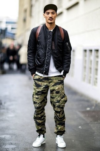 How to Wear Camouflage Pants In Spring For Men: A black bomber jacket and camouflage pants are a combo that every modern gent should have in his wardrobe. Complement this ensemble with a pair of white leather low top sneakers for a sense of refinement. And if you're looking for a killer look that will take you from winter to spring, this one fits the bill.