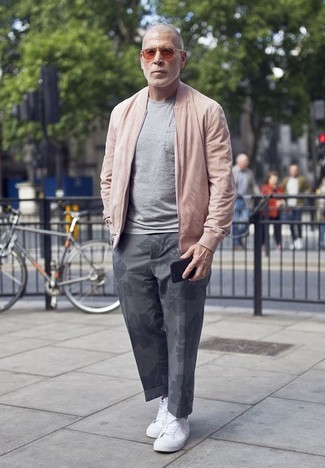 How to wear: pink bomber jacket, grey crew-neck t-shirt, grey floral chinos, white canvas low top sneakers