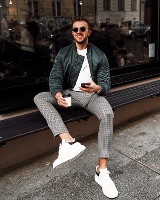 How to wear: dark green bomber jacket, white and black print crew-neck t-shirt, grey houndstooth chinos, white and black leather low top sneakers