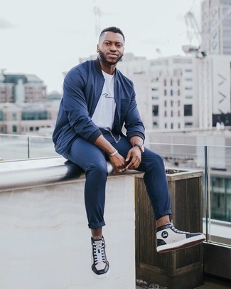 White and Black Leather Shoes with Pants Outfits For Men: This off-duty combo of a navy vertical striped bomber jacket and pants can take on different forms depending on the way you style it out. White and black leather high top sneakers are the simplest way to transform your outfit.
