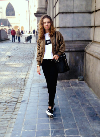 How to wear: brown bomber jacket, white and black print crew-neck t-shirt, black jeans, black and white athletic shoes