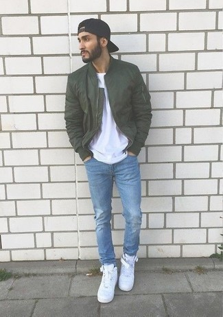 How to Wear White Leather High Top Sneakers For Men: This combo of a dark green bomber jacket and light blue jeans is indisputable proof that a pared down casual look can still look really interesting. If you need to easily play down this outfit with one single item, complement your outfit with a pair of white leather high top sneakers.