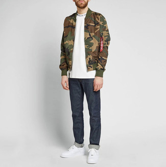 White and Red Leather Low Top Sneakers Outfits For Men: An olive camouflage bomber jacket and navy jeans are indispensable menswear must-haves to have in the casual part of your wardrobe. A pair of white and red leather low top sneakers is the glue that brings your getup together.