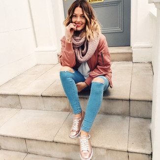 How to wear: brown bomber jacket, light blue crew-neck t-shirt, blue ripped skinny jeans, gold leather low top sneakers