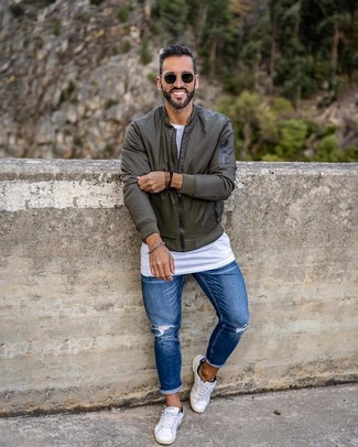 How to wear: olive bomber jacket, white crew-neck t-shirt, blue ripped skinny jeans, white low top sneakers