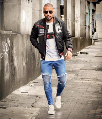 How to wear: black print bomber jacket, white print crew-neck t-shirt, blue skinny jeans, white leather low top sneakers