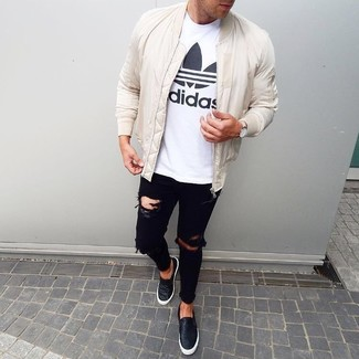 How to wear: white bomber jacket, white and black print crew-neck t-shirt, black ripped skinny jeans, black leather slip-on sneakers