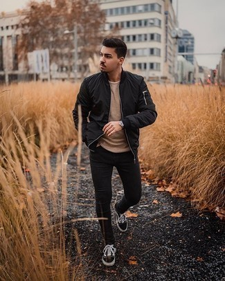 Black Bomber Jacket with Black Skinny Jeans Outfits For Men: Stylish yet practical, this look combines a black bomber jacket and black skinny jeans. A pair of black and white canvas low top sneakers will tie the whole thing together.